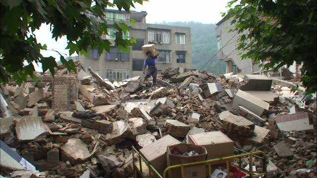 a man carries luggage as he climbs over a pile of rubble following an earthquake - 四川省点の映像素材/bロール