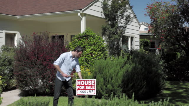"ms man carries out ""house for sale"" sign and planting into front lawn / santa monica, ca, united states - street name sign stock-videos und b-roll-filmmaterial"