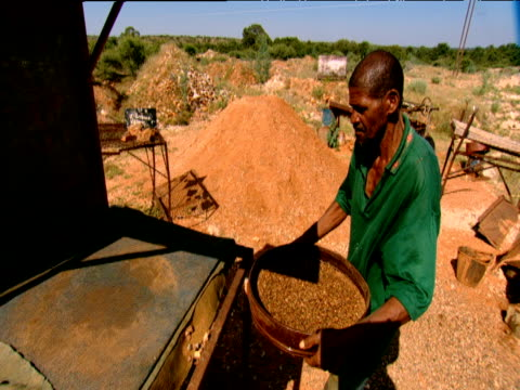 vidéos et rushes de man carries sieve over to counter and unloads stones and diamonds kimberley south africa - mine