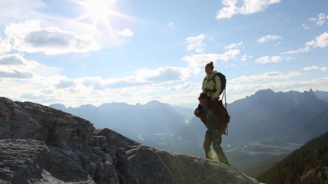 man carries woman on shoulders to mtn summit - shoulder ride woman stock videos & royalty-free footage