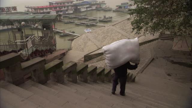 WS POV Man carriying enormous sack on shoulder / Chongqing, Sichuan Province, China