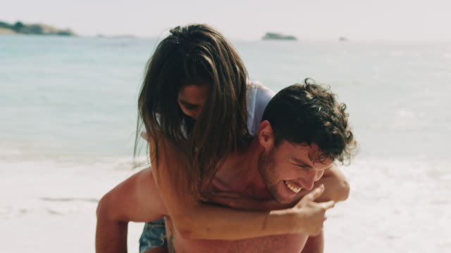 vídeos de stock e filmes b-roll de man carry his girfriend piggyback at the beach - namorado