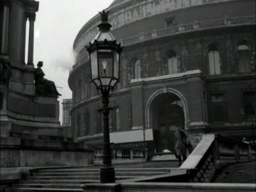 stockvideo's en b-roll-footage met man carrying a cello walks down steps outside the royal albert hall. - royal albert hall
