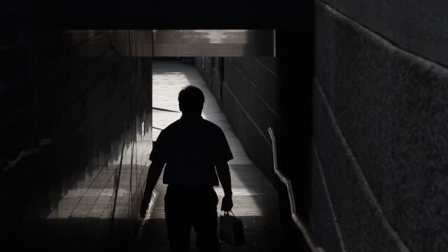 vídeos de stock, filmes e b-roll de a man carrying a shopping bag is silhouetted walking through a tunnel near the cheonggyecehon stream in seoul south korea on friday aug 28 a woman... - tunnel
