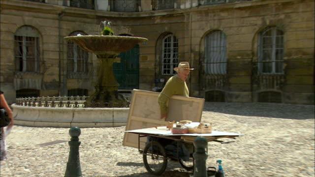 vídeos de stock, filmes e b-roll de ms zo man carrying artist's canvas near water fountain / aix-en-provence, provence, france - aix en provence