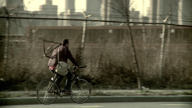 ms pan man carrying bicycle frame riding bicycle on street with cityscape in background, brooklyn, new york city, new york state, usa - bicycle frame stock videos & royalty-free footage