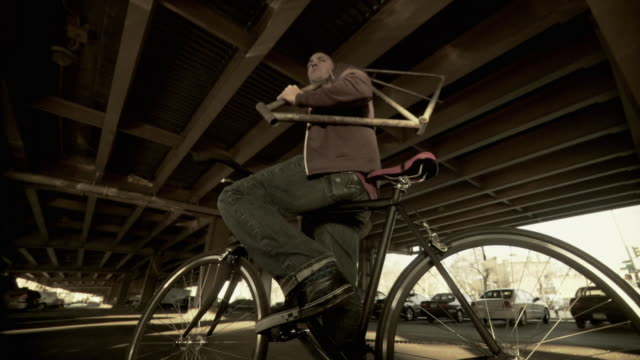 ms la man carrying bicycle frame riding bicycle under overpass, brooklyn, new york city, new york state, usa - bicycle frame stock videos & royalty-free footage