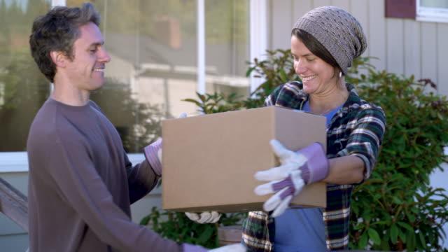 vidéos et rushes de man carrying box through doorway of house. - couple d'âge moyen