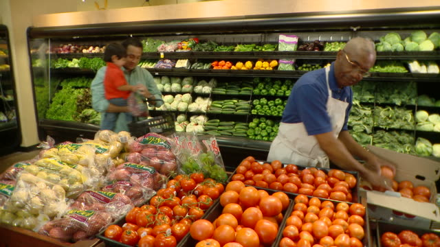 MS Man carrying boy (2-3) shopping in greengrocer's shop next to sales clerk unloading tomatoes, Richmond,  Virginia, USA