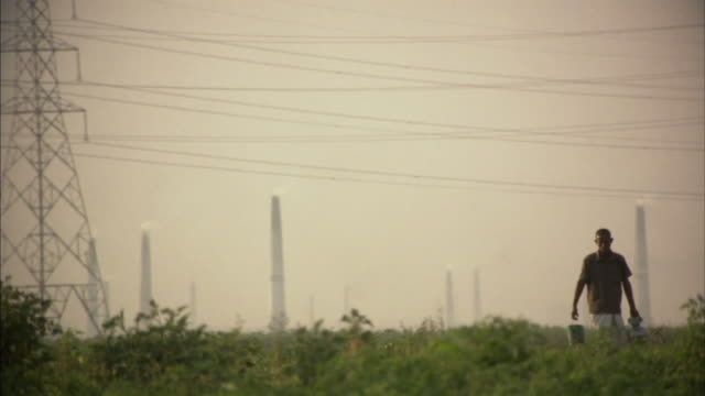 ws, selective focus, man carrying bucket and jug walking across field with smoke stacks in background, bangladesh - smoke stack stock videos & royalty-free footage