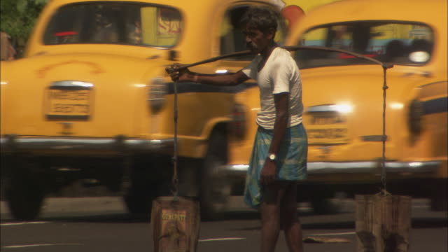 Man carrying buckets waits on edge of road for gap in busy traffic Available in HD.