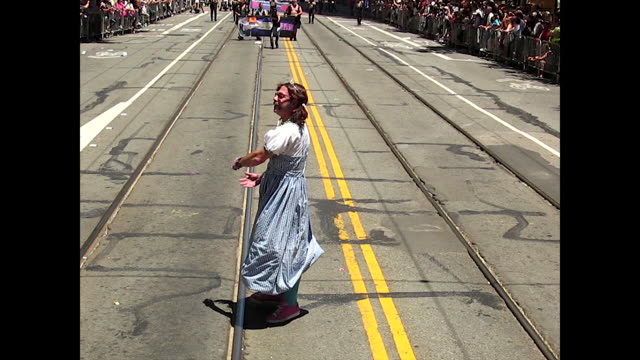 man carrying camera and another man carrying cords on the street, camera on crane; pride flag in the wind; man in cute blue dress and tiara on the... - kopfbedeckung stock-videos und b-roll-filmmaterial