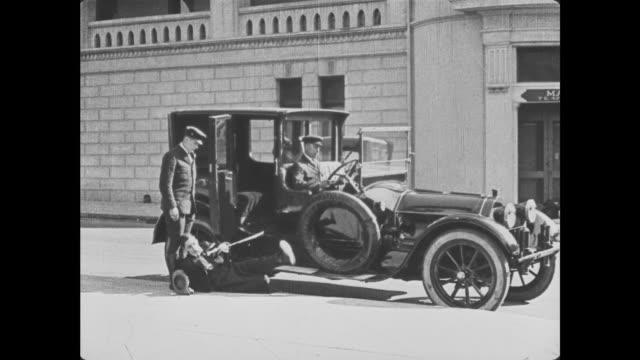 vidéos et rushes de 1921 man (buster keaton) carrying cane falls getting out of car - 1920