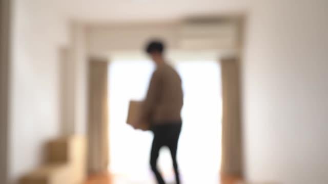 stockvideo's en b-roll-footage met mens die kartondozen draagt, die zich in een nieuw appartement bewegen. gedefocust - merchandise