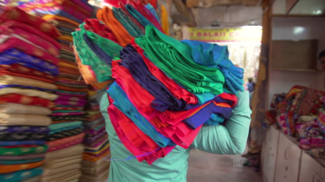 vídeos de stock, filmes e b-roll de man carrying clothing at india silk clothing shop market - vendedor trabalho comercial