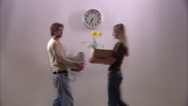 vídeos de stock, filmes e b-roll de man carrying computer monitor and woman carrying flowers in cardboard box passing in front of clock at end of work day and turning back to look at each other - amor à primeira vista