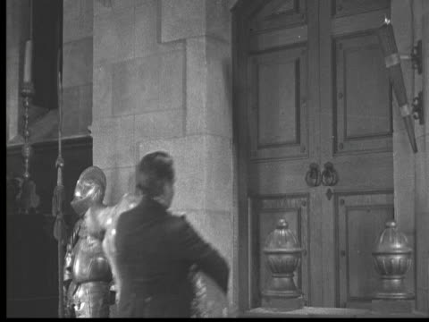vidéos et rushes de 1925 ms b/w man carrying feinted woman in castle, other man crouching on ledge - 1925