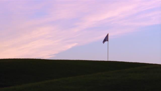 man carrying golf club walking across golf course at dawn - bandierina da golf video stock e b–roll