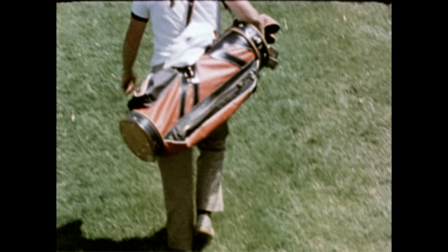 cu of man carrying golf clubs on his back / dozens of players and fans walking across the green / crowd huddled around single golfer / man hits ball... - anno 1958 video stock e b–roll