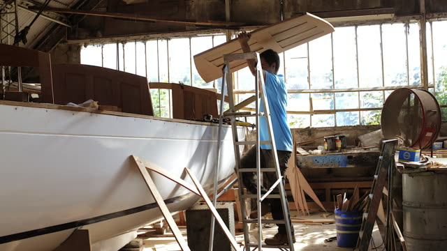 WS Man carrying hand made panels for renovated boat in workshop