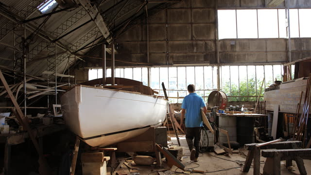 ws man carrying hand made panels for renovated boat in workshop - schiffswerft stock-videos und b-roll-filmmaterial