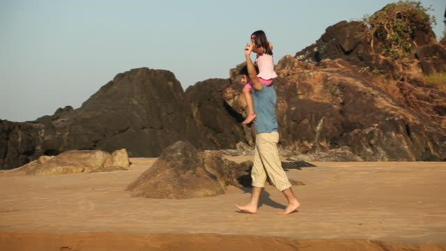 Man carrying her daughter on the coast