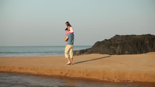 vídeos de stock e filmes b-roll de man carrying her daughter on the coast  - carregar uma pessoa nos ombros