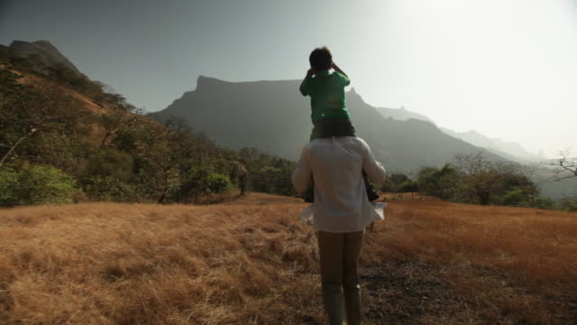 stockvideo's en b-roll-footage met man carrying his son on his shoulder in the forest - familie met één kind