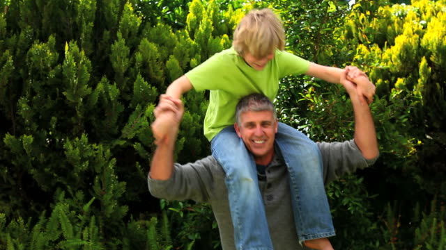 Man carrying his son on his shoulders in the garden / Cape Town, Western Cape, South Africa