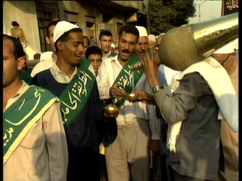 man carrying large flask on shoulder pours water into small metallic bowls for line of muslim men during maulid festival celebrating birth of prophet mohammed cairo - religious celebration stock videos & royalty-free footage