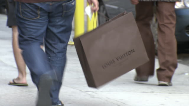 stockvideo's en b-roll-footage met cu, man carrying louis vuitton shopping bag walking on street, low section, fifth avenue, new york city, new york, usa - louis vuitton modelabel