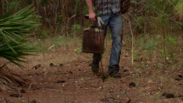 ms tu man carrying rusty canister and chain walking through forest, st. augustine, florida, usa - bombola video stock e b–roll