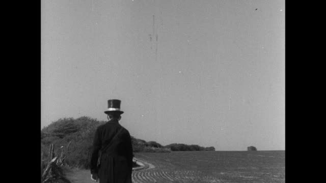 stockvideo's en b-roll-footage met montage man carrying satchel walking on grass and man in top hat walking along path by farmland/ england, united kingdom - 1935
