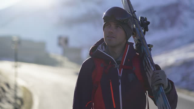 man carrying skis along a mountain pass in switzerland - ski holiday stock videos & royalty-free footage