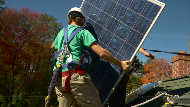 ms man carrying solar panel and placing it down on rope / greenfield, massachusetts, usa - putting stock videos & royalty-free footage