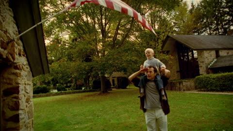 stockvideo's en b-roll-footage met ms, man carrying son (4-5 years) on shoulders saluting flag, usa, pennsylvania, solebury - salueren