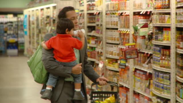 vídeos de stock, filmes e b-roll de ms pan selective focus man carrying son (2-3) shopping in supermarket, richmond,  virginia, usa - mamadeira