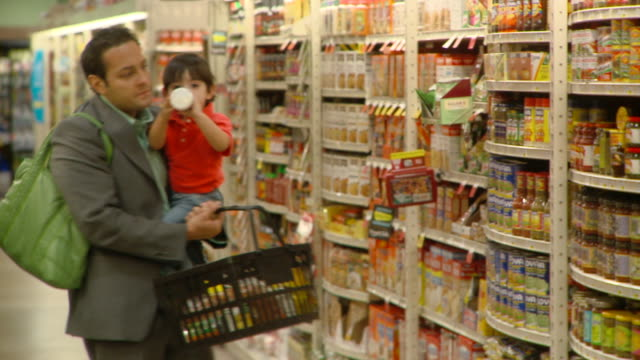 ms pan selective focus man carrying son (2-3) shopping in supermarket, richmond,  virginia, usa - スーパーマーケット点の映像素材/bロール