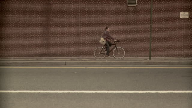 WS SLO MO Man carrying spare bike frame riding bicycle along brick wall, Brooklyn, New York City, New York State, USA