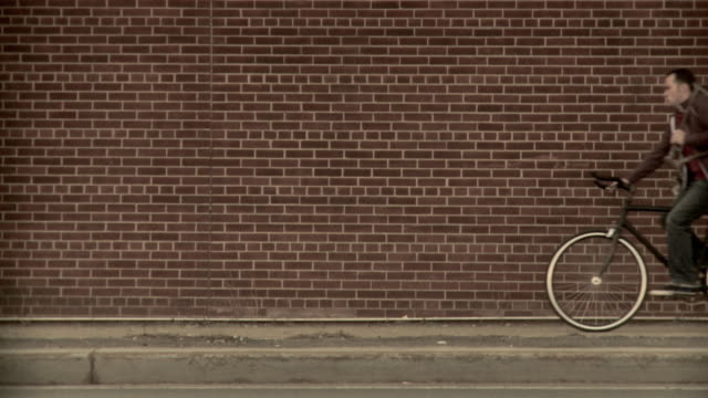 MS SLO MO Man carrying spare bike frame riding bicycle along brick wall, Brooklyn, New York City, New York State, USA