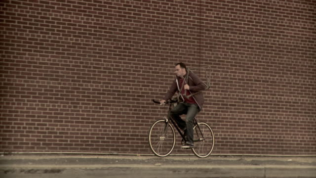 ms slo mo pan man carrying spare bike frame riding bicycle along brick wall, brooklyn, new york city, new york state, usa - 35 39 years stock videos & royalty-free footage