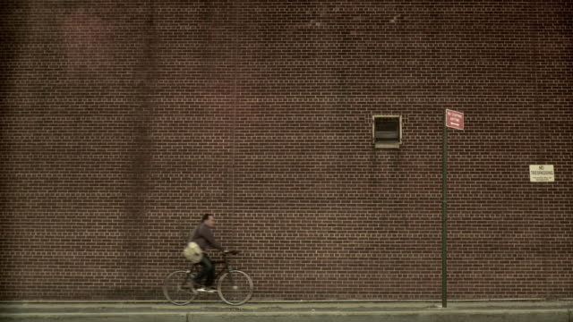 ms man carrying spare bike frame riding bicycle on sidewalk against brick wall, brooklyn, new york city, new york state, usa - pavement stock videos & royalty-free footage