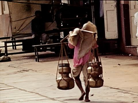 vídeos y material grabado en eventos de stock de 1939 ms man carrying stick on shoulders with jugs attached/ bombay, india  - menos de diez segundos
