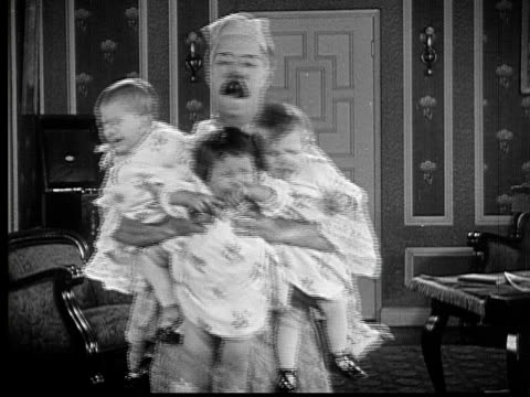 1925 b/w ms man (billy bevan) carrying three screaming babies strapped to chest and three more on his back / usa - large family stock videos & royalty-free footage