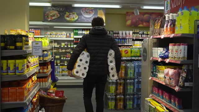 vídeos de stock, filmes e b-roll de homem carregando papel higiênico em um supermercado - grupo grande de objetos