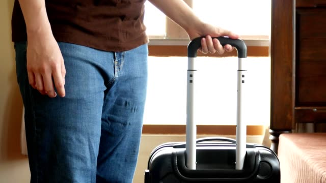 man carrying travel luggage out of bedroom for traveling