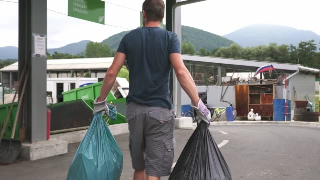 man carrying two garbage bags he needs to recycle - portare video stock e b–roll