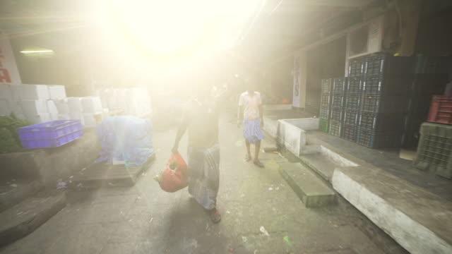 vídeos de stock e filmes b-roll de man carrying vegetables working at india market. steadicam shot - feirante