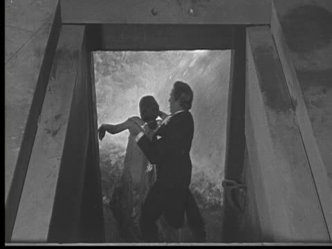 1925 ms b/w man carrying woman from flooded dungeon to room - wet stock videos and b-roll footage
