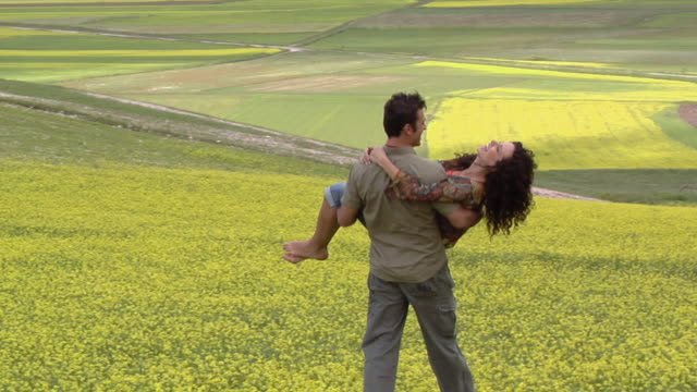 MS PAN WS TS Man carrying woman in his arms and walking in field of yellow wildflowers / Castelluccio, Norcia, Italy